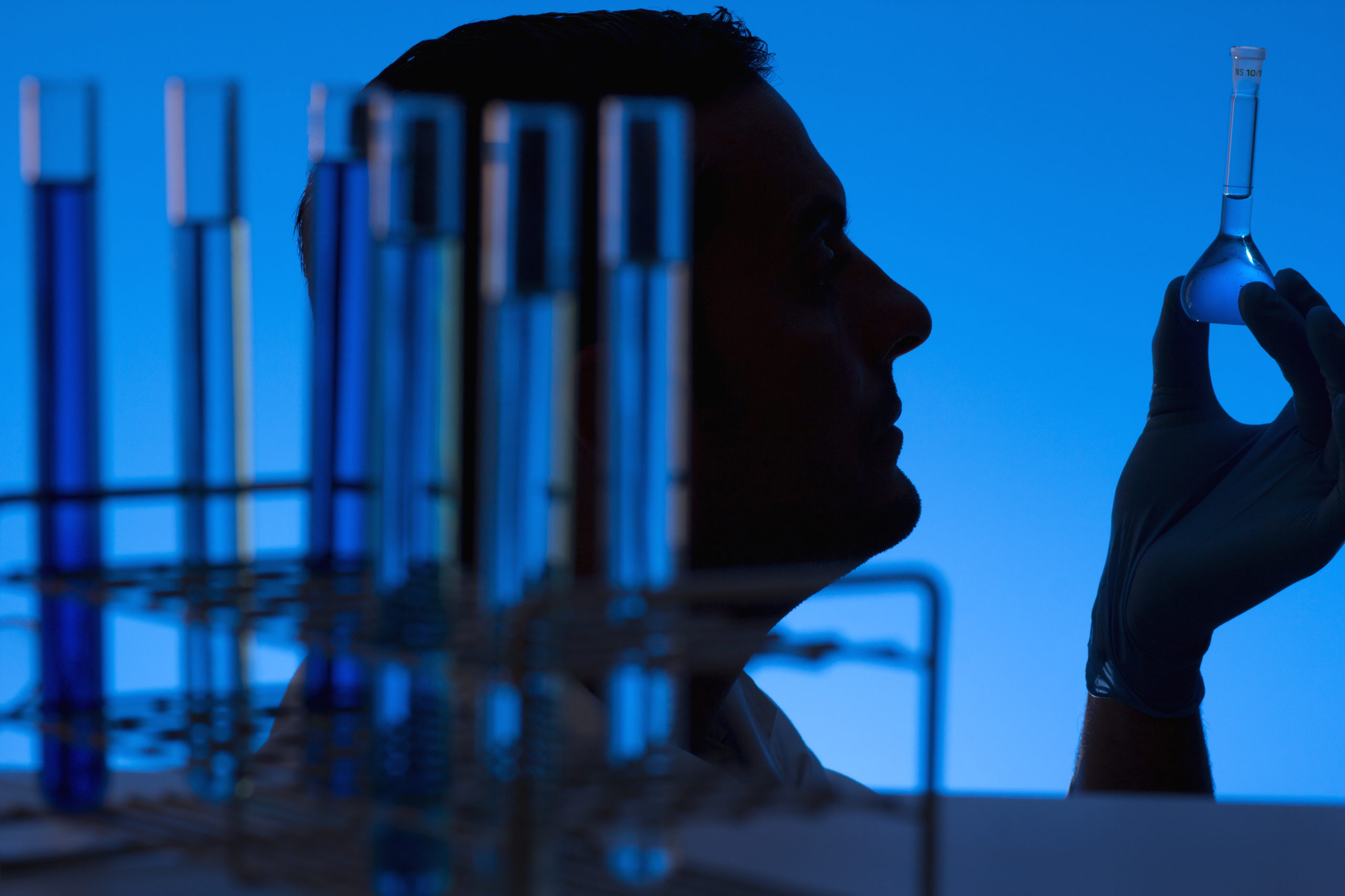 Researcher looking into a flask at the laboratory